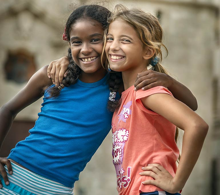 Young Cuban girls hugging.