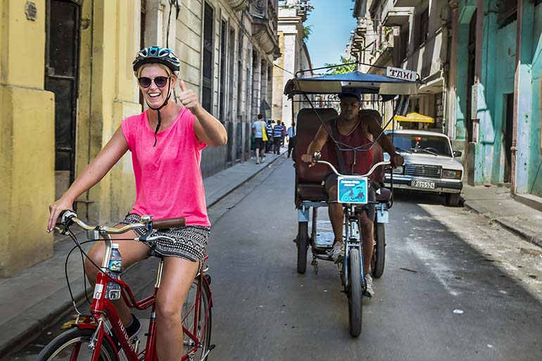 Woman biking in Old Havana.